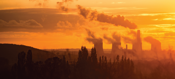Landscape of power plant in distance at sunset